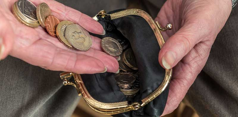 hands tipping coins into a purse
